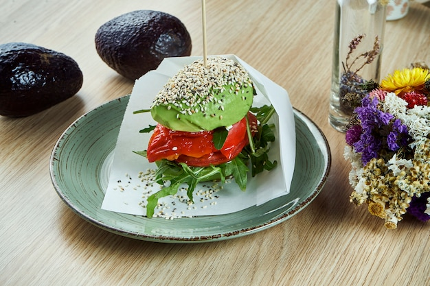 An unusual burger made from halves of avocado, like buns with tomato and ruccola, bell pepper. view. healthy and green food. vegan