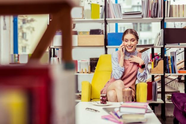 珍しいカフェ。ピンクのドレスの下にシャツを着て、スマートフォンで面白い会話をしている感動の少女