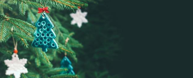Необычные керамические игрушки в виде снежинки и силуэта елки на еловой ветке. минималистичная концепция