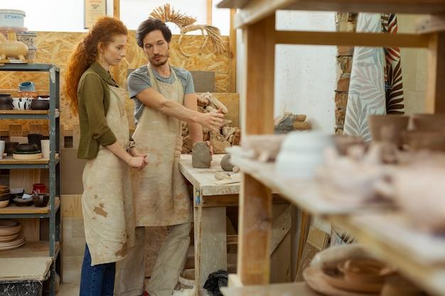 珍しい粘土片。個人レッスン中に気配りの行き届いた女性にプロセスを説明するスマートなプロの陶芸家