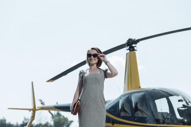 Необычная экскурсия. веселая молодая женщина проводит экскурсию по вертолетной площадке и счастливо улыбается, проверяя все