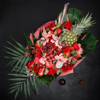 Unusual gift in the form of a bouquet of flowers and fruits. view from above