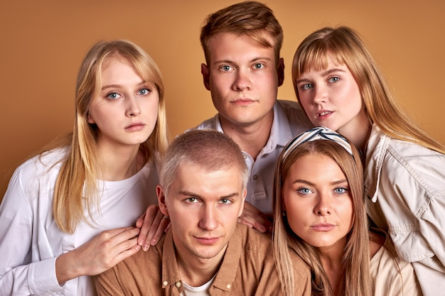 Необычная группа неординарной молодежи позирует в модной одежде, кавказские модели уверенно смотрят в камеру, изолированную в студии