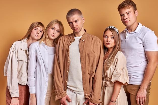 Необычная группа незаурядной молодежи, позирующих в модной одежде, кавказских моделей