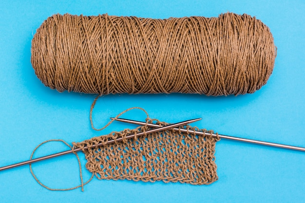 Unusual knitting of twine on knitting needles. knitted fabric, knitting needles and skein.