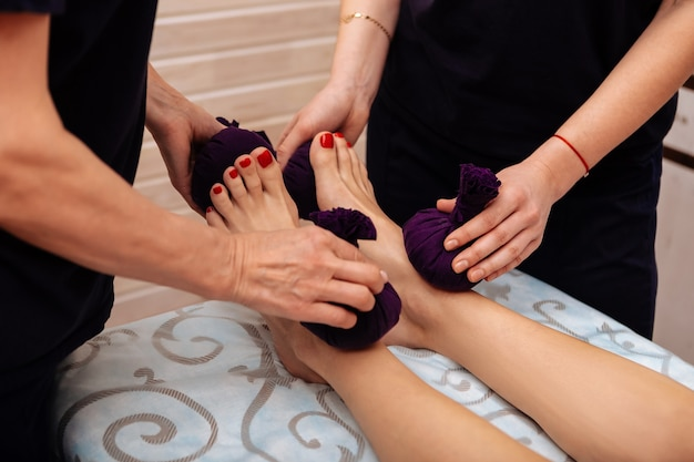 Unusual massage technique. hard-working women in black uniform massaging neat feet of their client with tight bags full of herbs