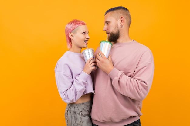 Необычная симпатичная женщина с короткими розовыми волосами и татуировкой пьет кофе и развлекается со своим парнем на оранжевом фоне
