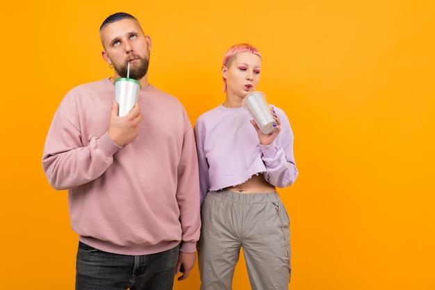 Необычная красотка с короткими розовыми волосами и татуировкой пьет кофе и развлекается со своим парнем на оранжевом