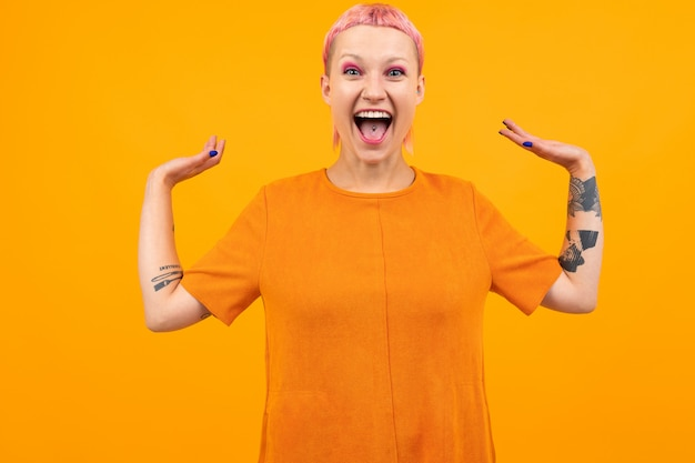 Unusual pretty woman with short pink hair and tattoo screams with happiness isolated on orange