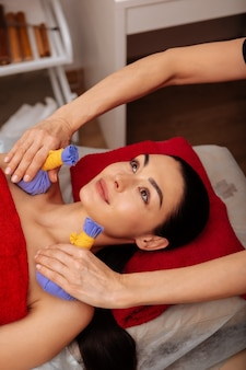 Unusual procedure. appealing long-haired lady resting on massage bad while master carefully touching her shoulders with equipment