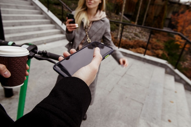 電動スクーターの珍しいロマンチックなデート。一人称ビュー。空白のコピースペース画面、一杯のコーヒーとホイールでスマートフォンを持っている男。電話を手に立って笑顔の女性。