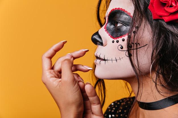 プロフィールに立っている若い黒髪の女性の珍しいショット。ハロウィーンの写真のための優雅な指のポーズでラティーナモデル