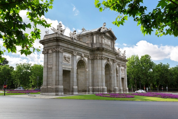 Unusual view of the puerta de alcala with the retiro park behind it. famous places of the city of madrid.