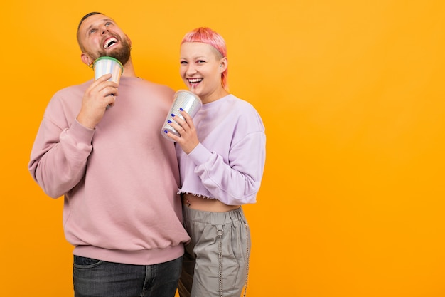 Unusual woman with short pink hair and tattoo drinks coffee and having fun with her boyfriend isolated on orange