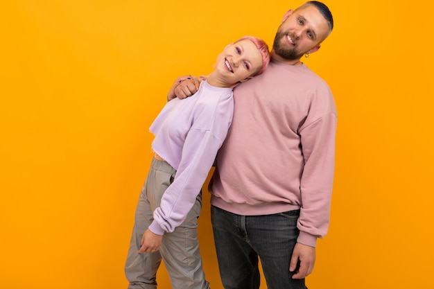 Unusual woman with short pink hair and tattoo enjoys life with her boyfriend isolated on orange
