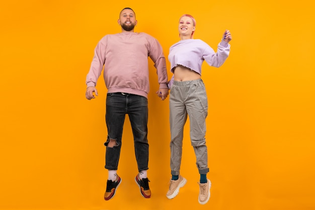 Unusual woman with short pink hair and tattoo having fun with her boyfriend isolated on orange