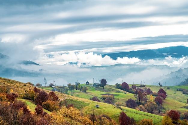 아름다운 언덕에 있는 카르파티아 산맥의 비정상적으로 아름다운 자연, 다채로운 숲과 작은 마을의 환상적인 하늘