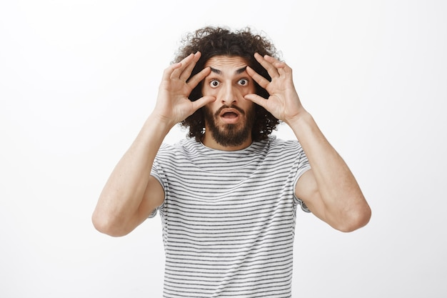 Unvelievable sales concept. stunned impressed handsome hispanic guy with beard and curly hair, holding eyelids with fingers
