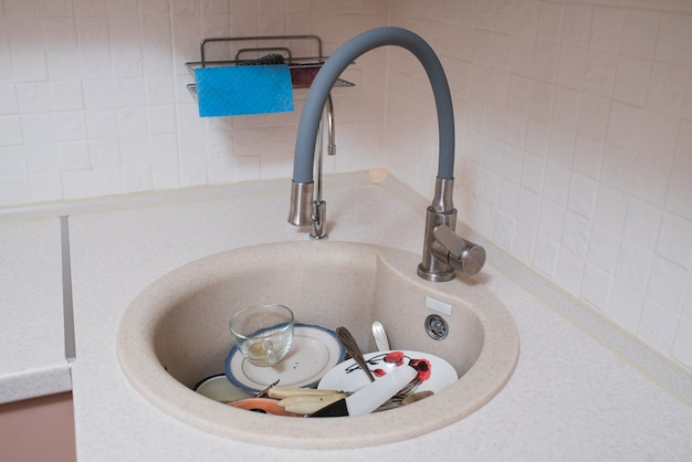 Немытая посуда в кухонной раковине. беспорядок, работа по дому.