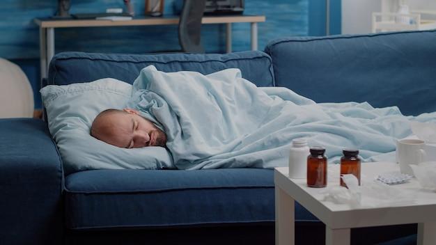 薬と一緒に寝ているソファに横たわっている体調不良の大人
