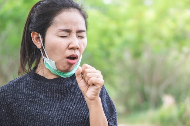 Unwell asian woman coughing outdoors