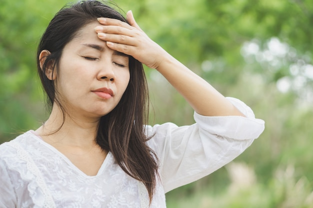 Unwell asian woman having headache outdoors
