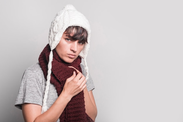 Unwell woman wearing scarf around her neck standing against gray background