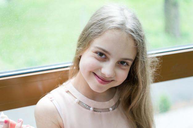 미소를 풀어보세요. 긴 금발 머리와 행복한 미소를 가진 사랑스러운 작은 아이. 큰 매력적인 미소와 함께 쾌활 한 어린 소녀입니다. 아름 다운 얼굴에 흰색 귀여운 미소로 웃는 아이.