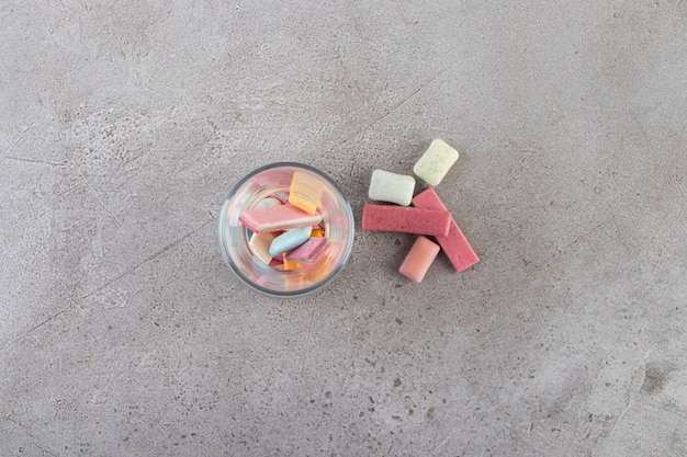 Unwrapped sugar free chewing gum sticks placed in glass.