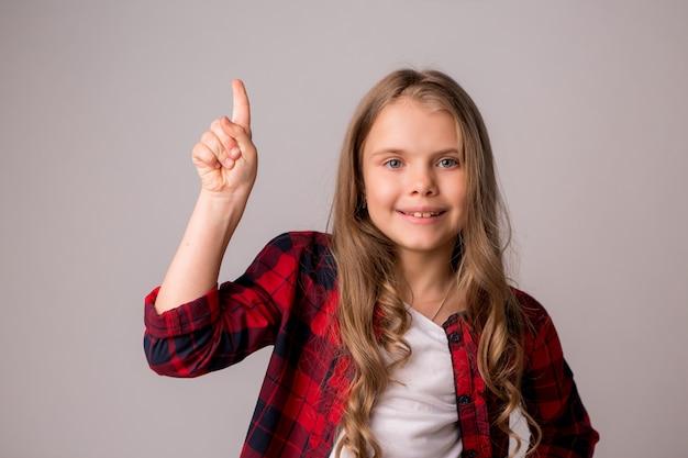 プレティーンの女の子笑顔と彼女の指でuoを指す