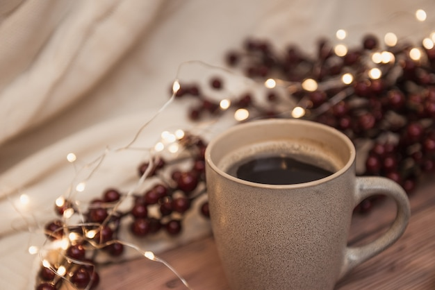 Ð¡up of coffee, christmas lights on background, selective focus. winter drinks backdrop.