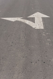 Up and left pointing arrows on asphalt