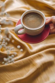 Чашка кофе в руках на золотой атласной ткани с цветами гипсофилы.