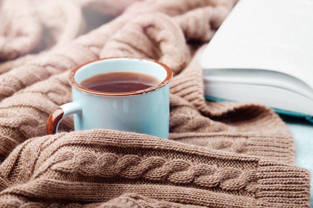 ?熱いお茶、開いた本、暖かいニット毛布のアップ