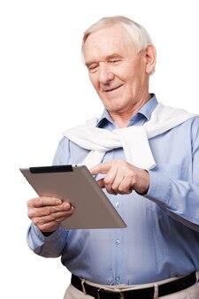 모든 연령대에서 최신 정보를 제공합니다. 흰색 배경에 서 있는 동안 디지털 태블릿을 들고 행복한 노인