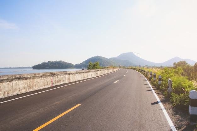 雲と青空の下で丘の緑の草の上の道。田舎道.upの丘道.vintage road。環境の道。自然の道.asphalt road。青空、雲、道。田舎の道路。ストレートロード。ロードビュー。
