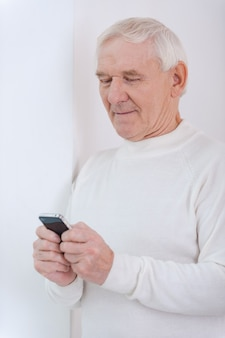 Up with times. confident senior man holding mobile phone while leaning at the wall