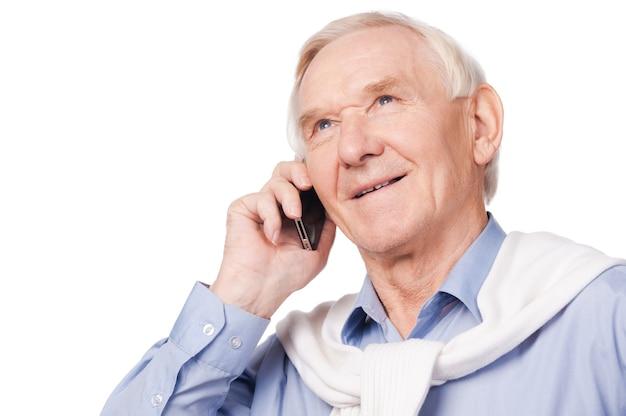 時代とともに。白い背景に立っている間カメラで笑って幸せな年配の男性の肖像画