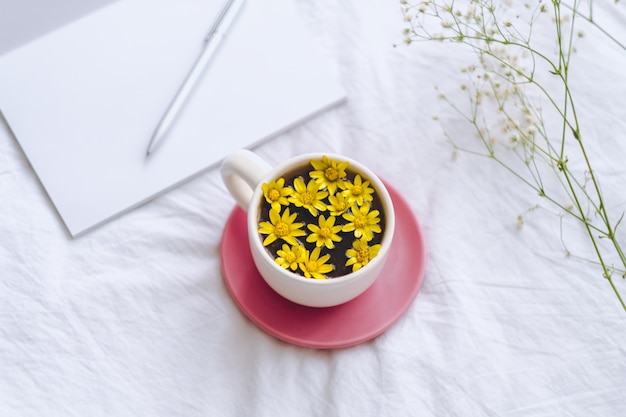 Ð¡up with yellow flowers inside, on a white bed with notepad and pen.