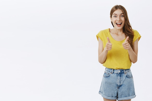 Upbeat beautiful girl showing thumbs-up in approval, like idea, agree or recommend something awesome