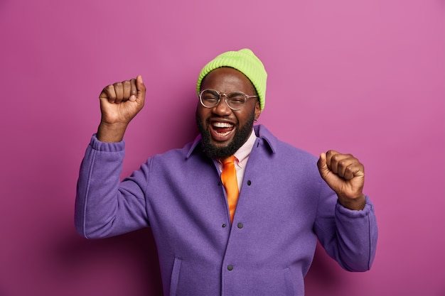 Upbeat carefree black bearded man dances with clenched fists, has carefree mood, cheers and moves actively, rejoices nice event, wears fashionable bright clothes, enjoys pleasant music and tunes.