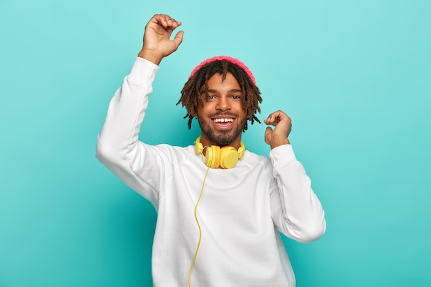 Upbeat carefree mixed race guy dances with hands up, listens awesome music track via headphones, has dreads, wears white comfortable jumper and stylish hat