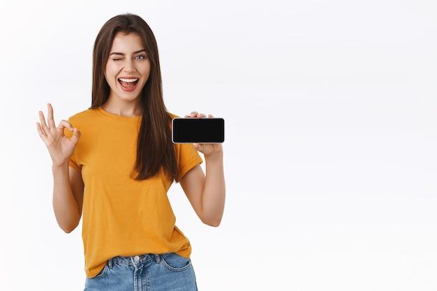 스마트폰을 가로로 들고 있는 노란색 티셔츠를 입은 쾌활하고 밝은 갈색 머리 여성은 괜찮고, 훌륭한 제스처와 윙크를 하고, 만족스러운 미소로 응용 프로그램이나 모바일 게임을 홍보합니다.