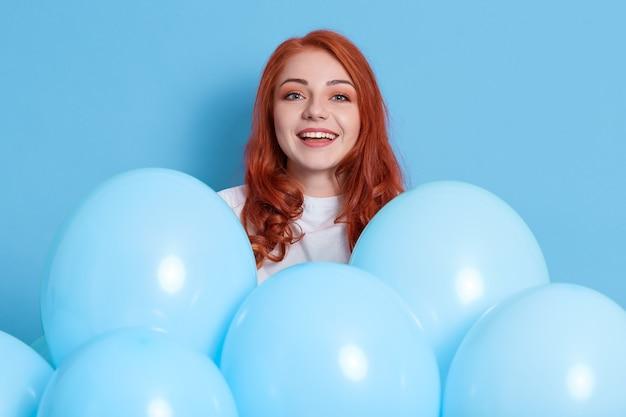 明るい陽気な赤い髪の女性は非常に幸せで興奮していると感じ、パーティーで自由な時間を過ごし、白いシャツを着て、青い壁に隔離された風船の近くでポーズをとり、興奮した生姜の女の子がカメラを見ます。