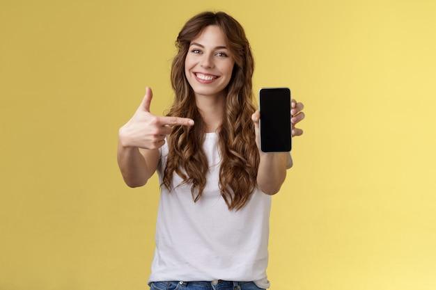 Оптимистичная, уверенная в себе красивая женщина, показывающая фотографию на дисплее смартфона, поднесите мобильный телефон протянутой рукой камера, указывая указательным пальцем на экран мобильного телефона, улыбается, довольная, продвигает приложение, интернет-приложение
