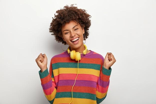 경쾌한 어두운 피부를 가진 여성은 기쁨으로 춤을 추고, 주먹을 움켜 쥐고, 성공과 승리를 축하하고, 화려한 스웨터를 입고, 넓게 미소를지었습니다.