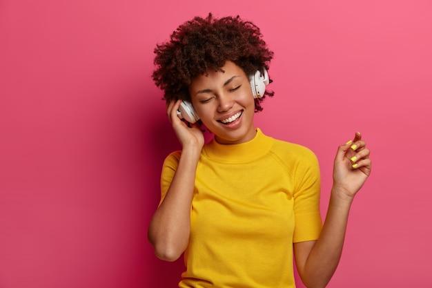 Una ragazza etnica allegra si muove spensierata e ascolta la musica in cuffia, si sente rilassata, gode della melodia preferita o della nuova traccia sull'app delle canzoni, indossa abiti gialli, isolata sul muro rosa. tecnologia, gadget
