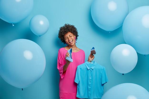 Allegra splendida donna con i capelli afro sceglie l'abito per un appuntamento romantico, si vanta di nuovi vestiti e scarpe acquistati in vendita in un negozio di abbigliamento, canta spensierata, tiene la camicia sulle grucce, isolato su blu