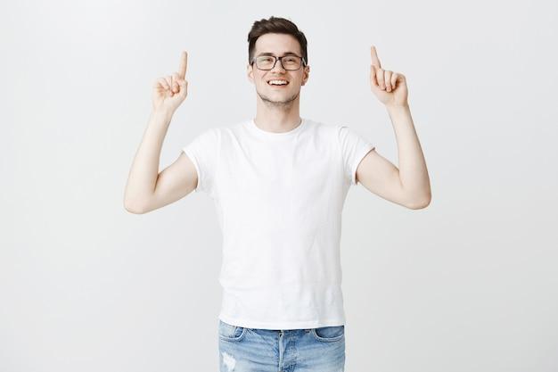 Allegro bel giovane con gli occhiali che punta il dito verso l'alto