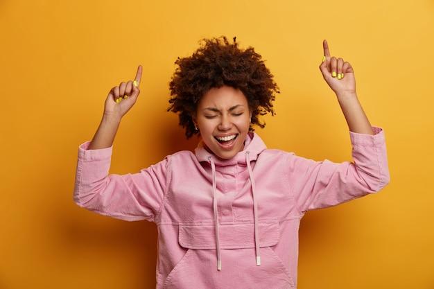 Жизнерадостная радостная афроамериканка поднимает руки и указывает выше